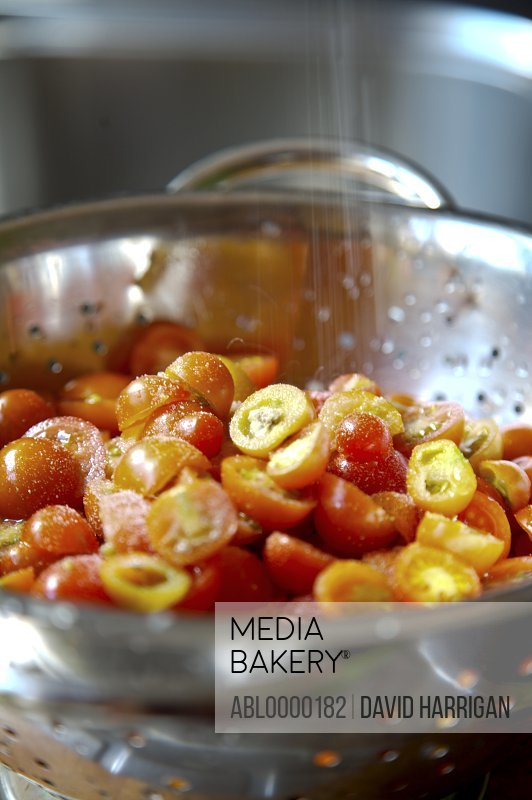 Close up of cherry tomatoes and salt in a colander