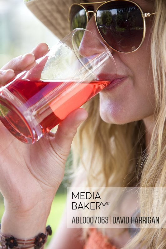 Woman Wearing Aviators Drinking Cranberry Juice