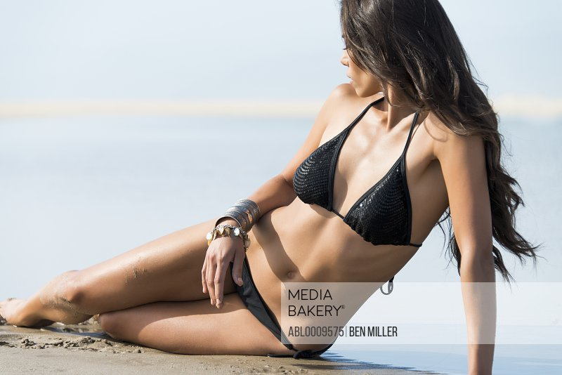 Woman Wearing Black Bikini Lying on Beach