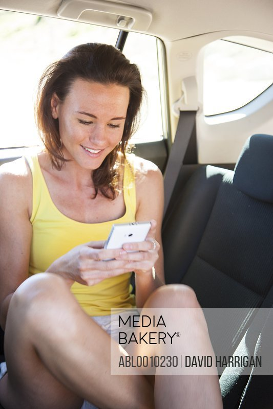 Woman inside Car Using Smart Phone