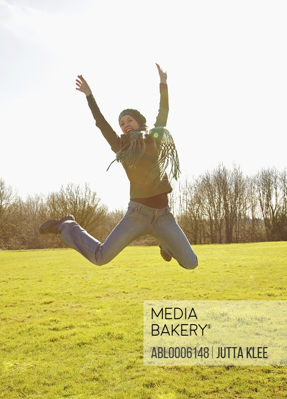 Woman jumping mid air with arms over head