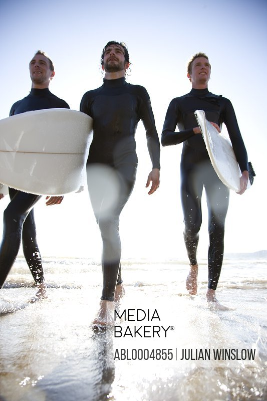 Three surfers walking out of the sea holding surfboards
