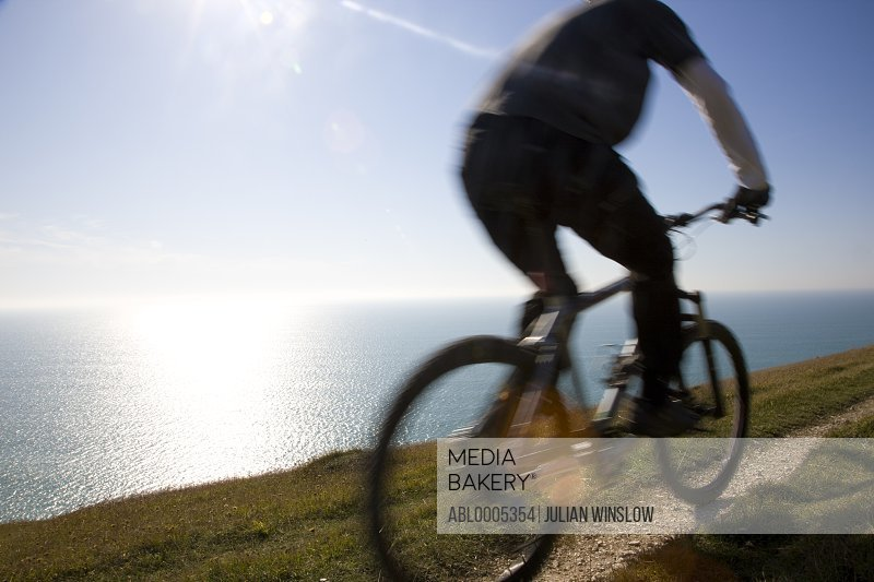 Back view of a man cycling on a costal path by the ocean