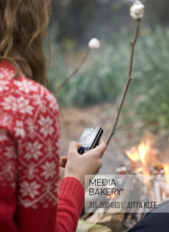 Back view of teenaged girl roasting marshmallow over campfire using cell phone
