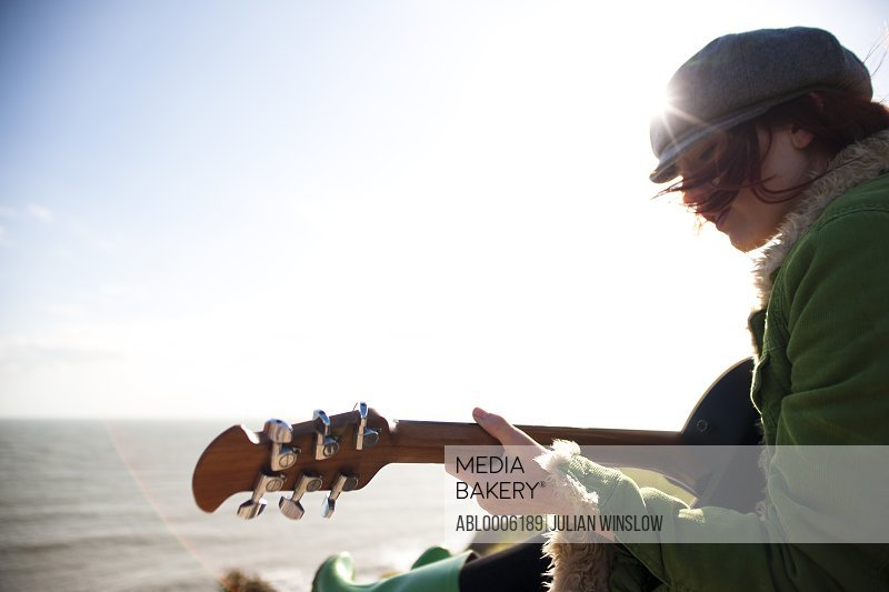 Young woman playing guitar by the ocean