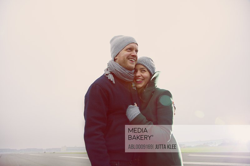 Smiling Couple Embracing  on Airport Runway