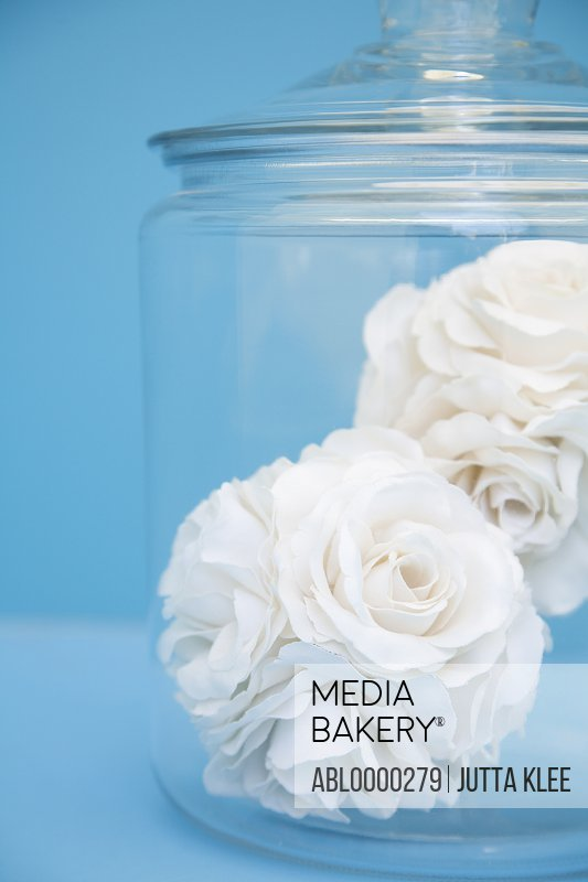 Close up of two fabric white roses in a clear glass jar
