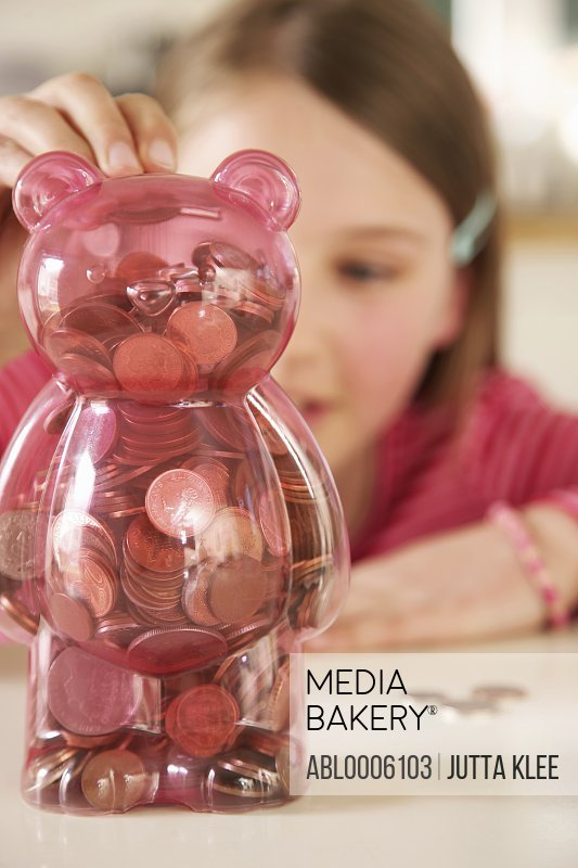 Girl putting coins into a money box in the shape of a teddy bear
