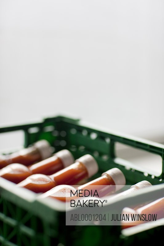 Close up of a plastic crate filled with tomato sauce bottles