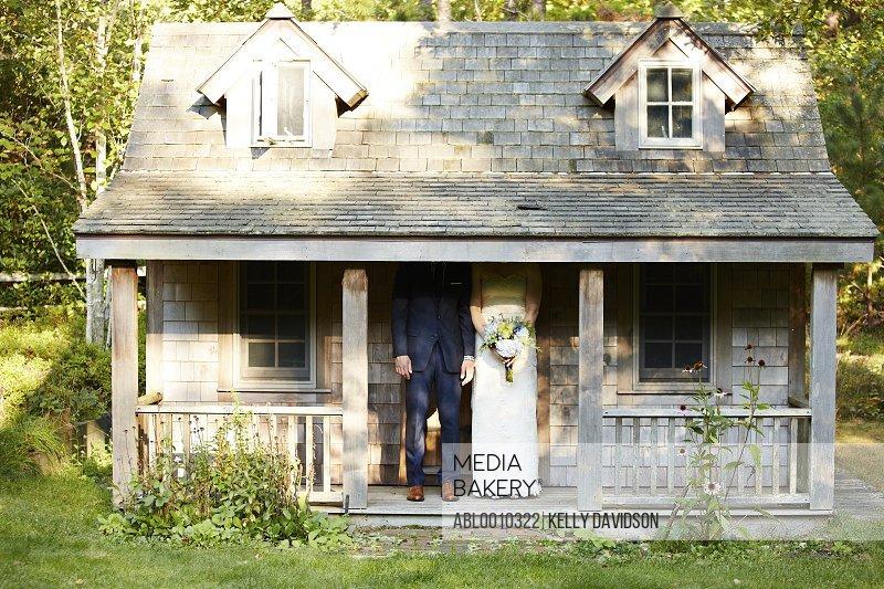 Bride and Groom Standing under Garden Cottage Porch