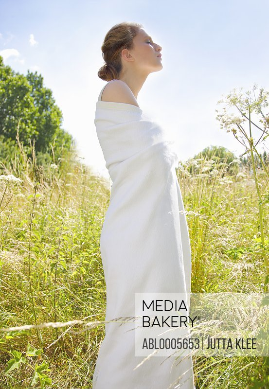 Profile of a young woman standing in a field wrapped in a white pashmina