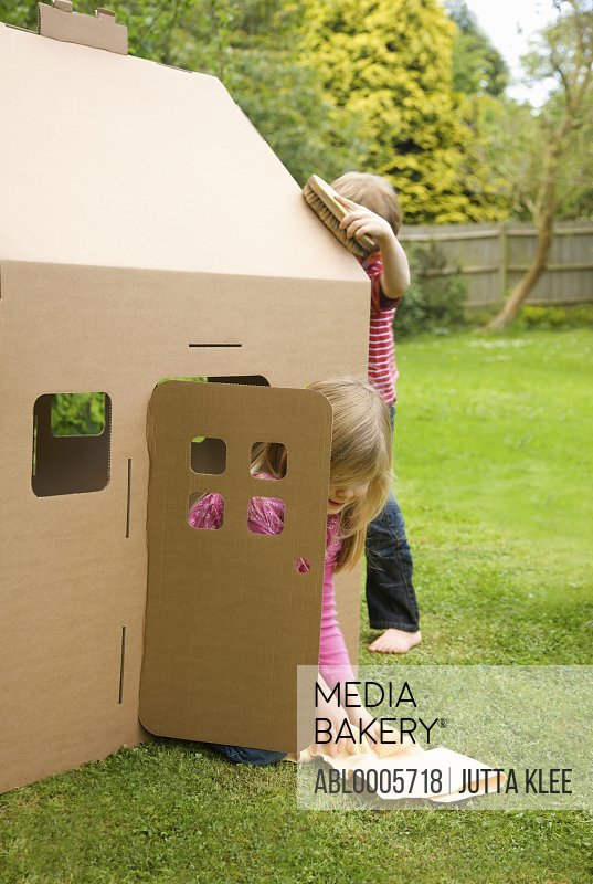 Boy and girl playing and cleaning the outside of a cardboard playhouse