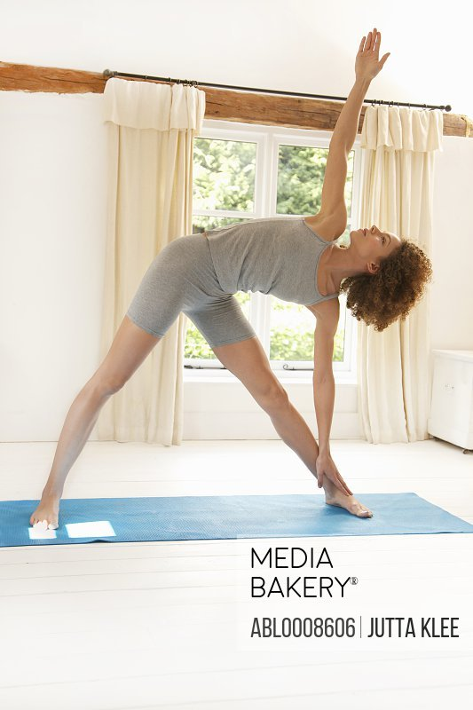 Woman Practicing Yoga in the Triangle Pose
