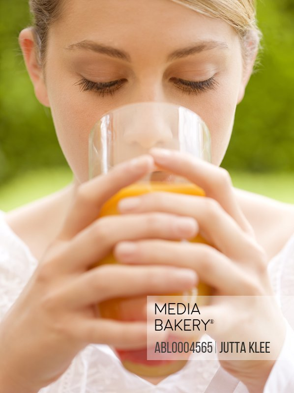 Close up of a young woman drinking and holding a glass of orange juice