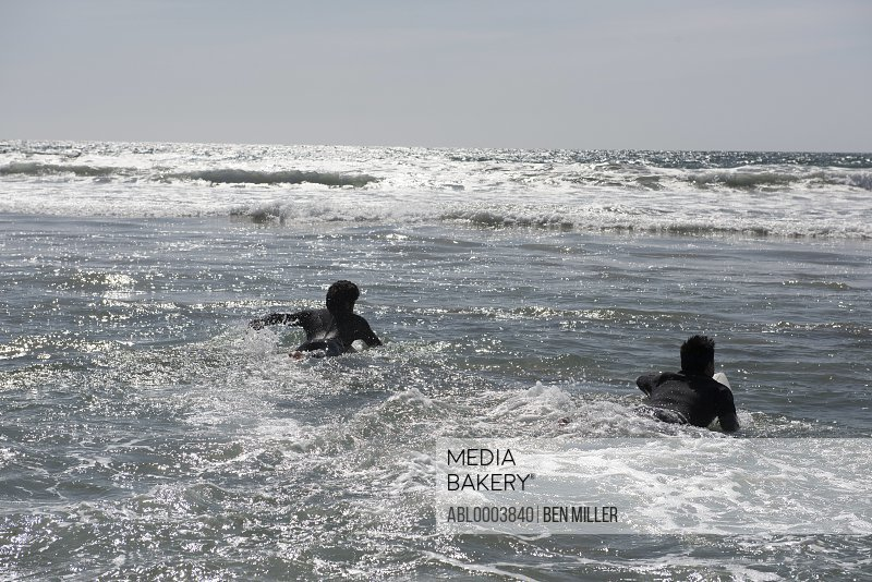 Back view of Two Male Surfers Paddling into the waves