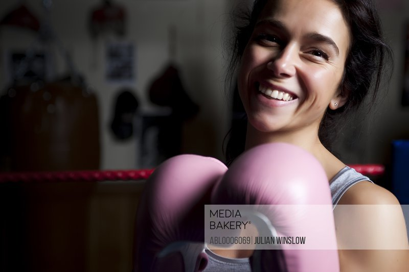 Woman wearing pink boxing gloves smiling