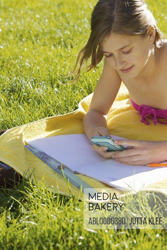Girl Revising Outside Using Cell Phone
