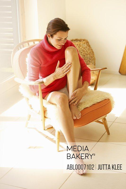 Woman Sitting on Armchair Massaging her Leg
