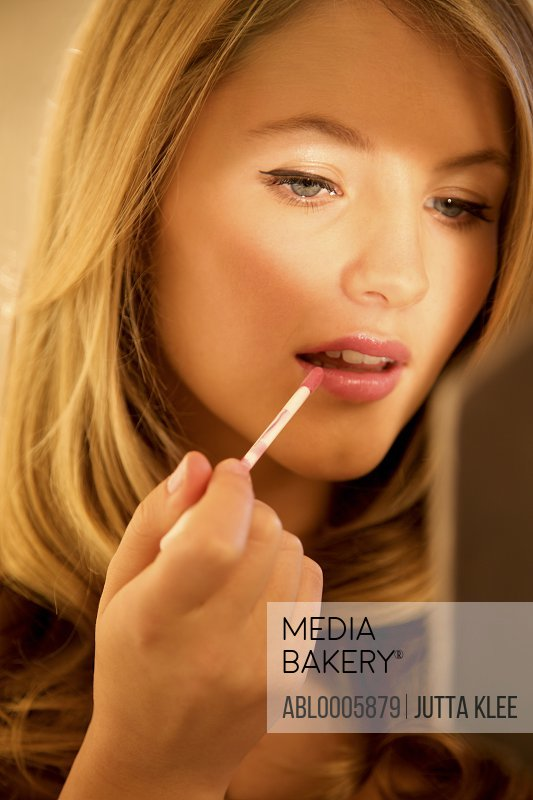 Close up of a young woman applying lip gloss