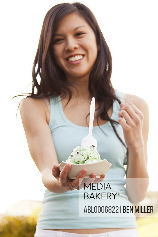 Smiling Young Woman Holding Bowl of Ice Cream Outdoors