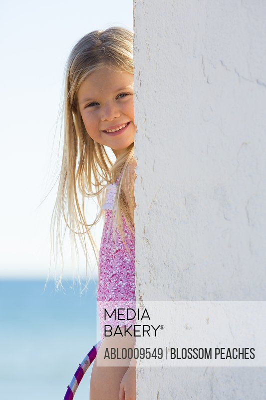 Girl Partially Obscured by Wall Smiling, Sea in Background