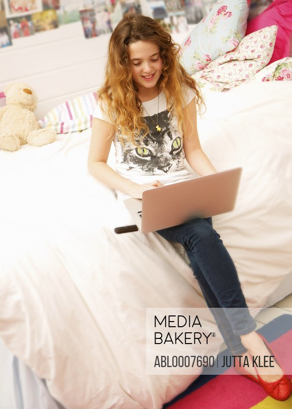 Young Girl Sitting on Bed Using Laptop