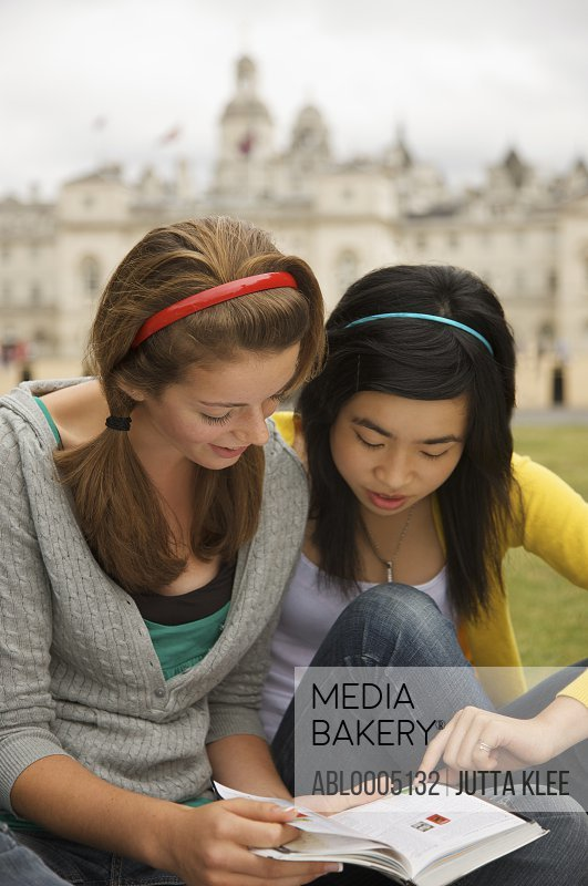Two teenaged girl reading a book in front of  London Horse Guards Parade