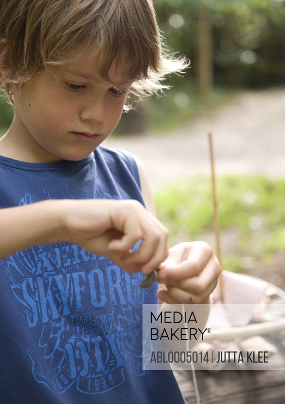 Young boy tying a knot with a string around a stone