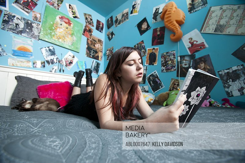 Teenage Girl Lying in Bed Reading