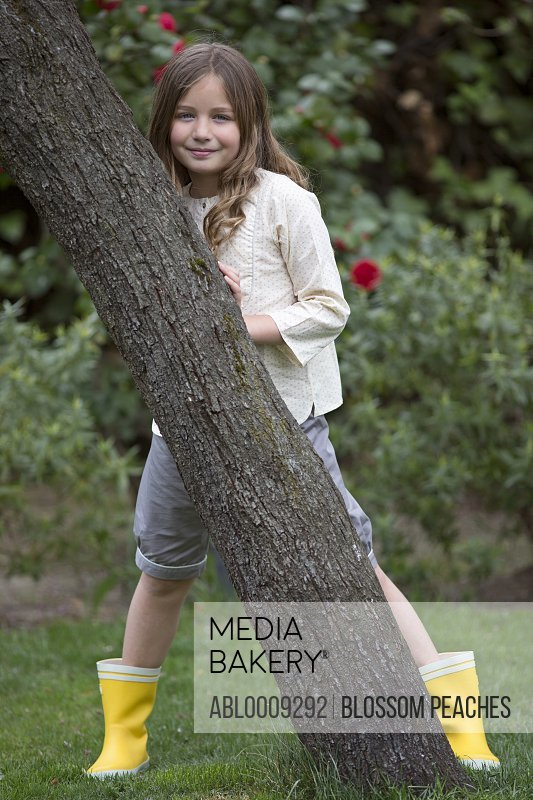 Young Girl Standing behind tree