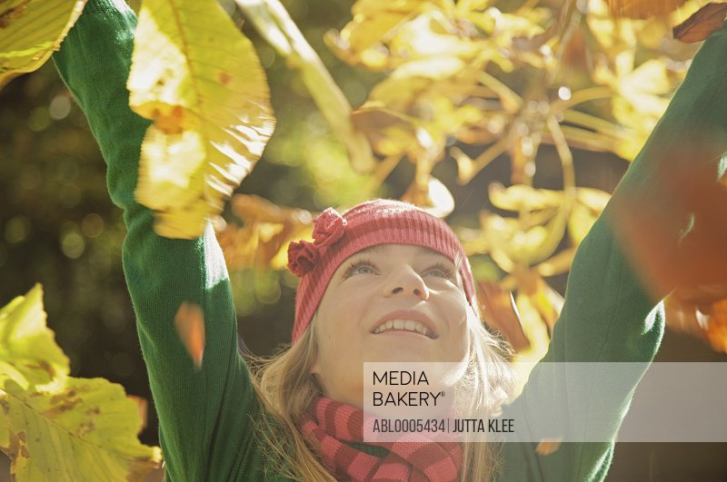 Close up of a smiling young girl with her arms in the air surrounded by leaves
