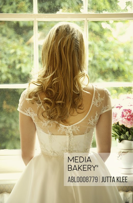 Back View of Young Bride Looking Out of Window
