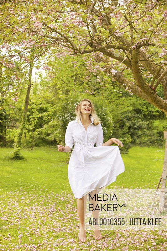 Smiling Young Woman Jumping under Tree in Garden