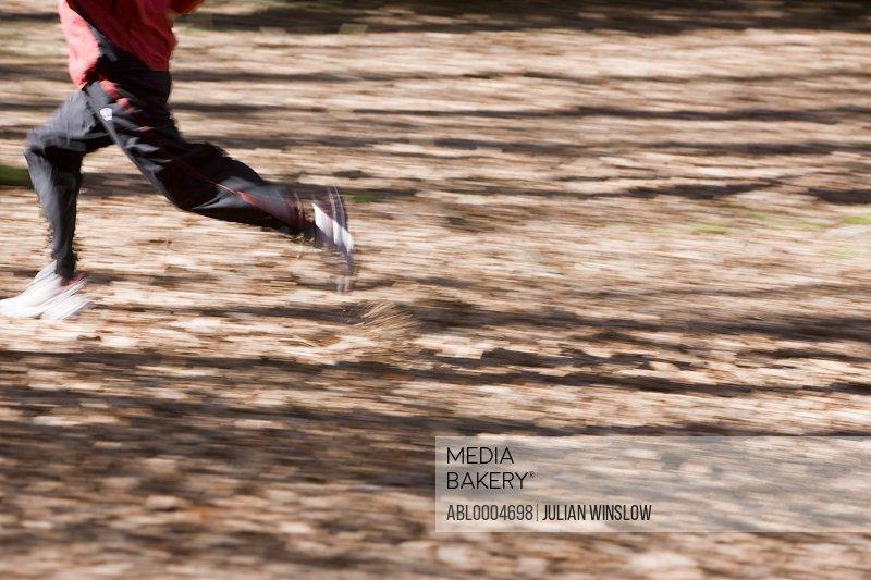Portrait man legs running in the park