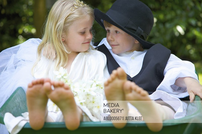 Boy and a girl wearing bride and groom costumes sitting in a wheelbarrow