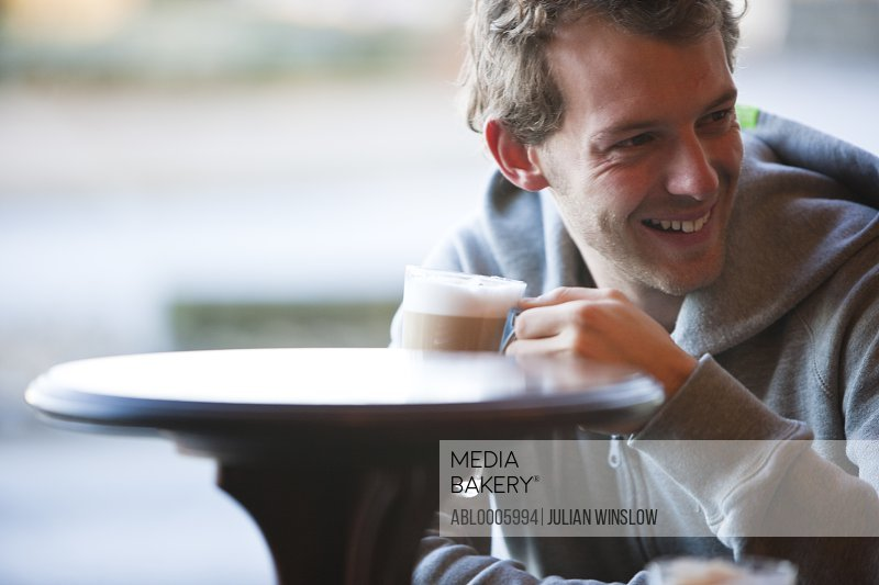 Smiling young man having a latte