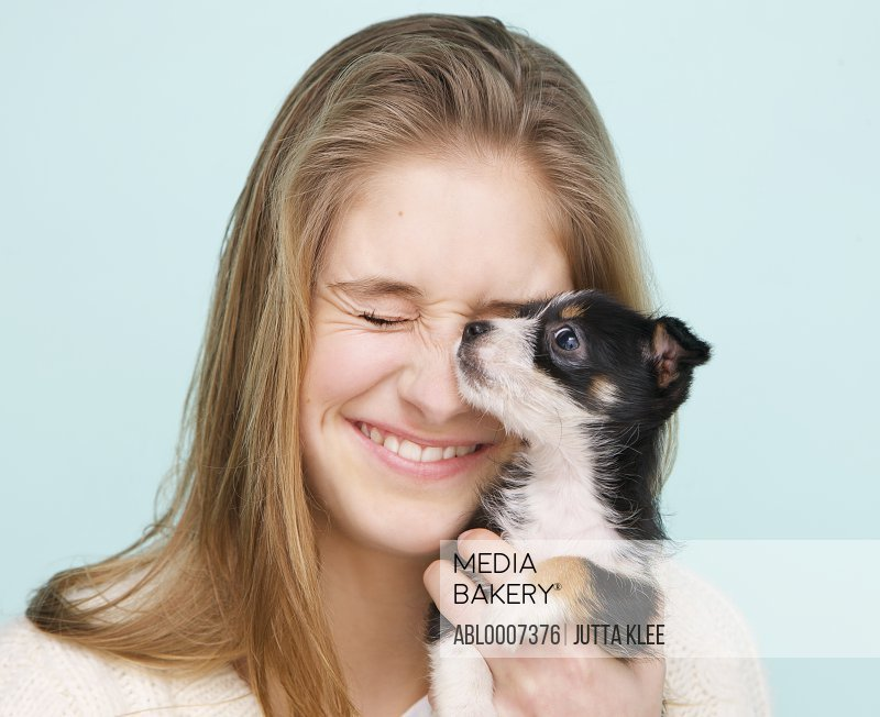 Smiling Teenage Girl Hugging Tiny Puppy