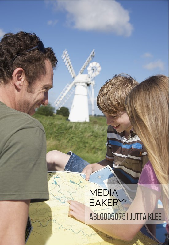 Man and children looking at a map
