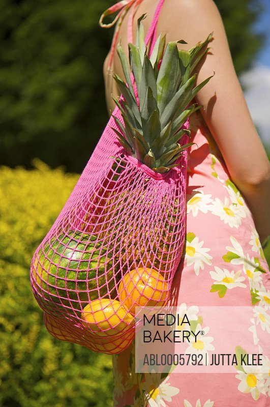 Woman carrying a shopping bag full of fruit