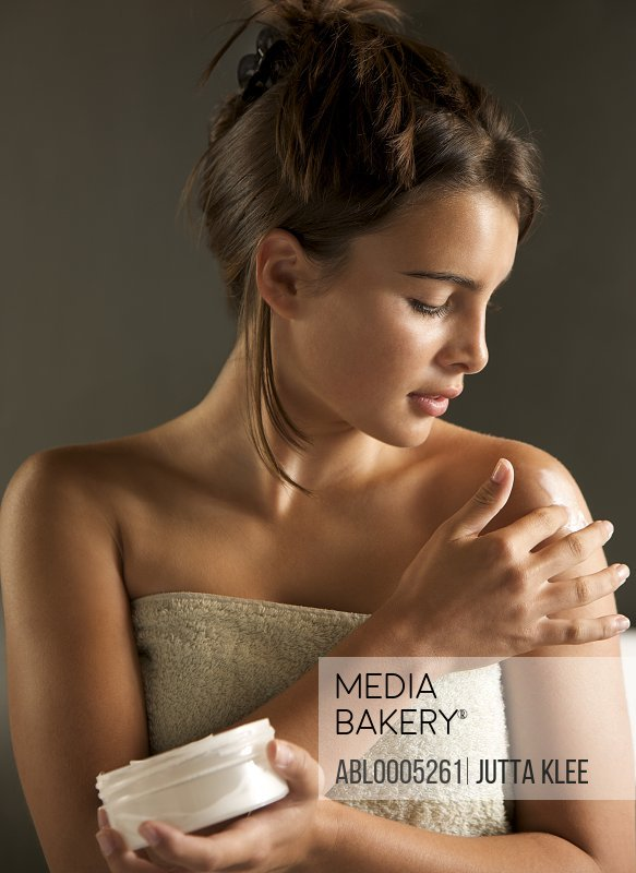 Young woman wrapped in a towel holding cream jar and rubbing her shoulder with body lotion