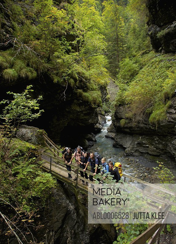 Group of Hikers Standing on Bridge over Gorge in Bernese Oberland