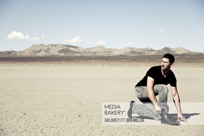Man Crouching in Desert Landscape