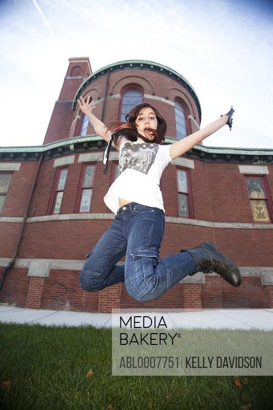 Teenage Girl Jumping Mid Air Outdoors