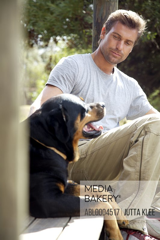 Man sitting under porch with his dog