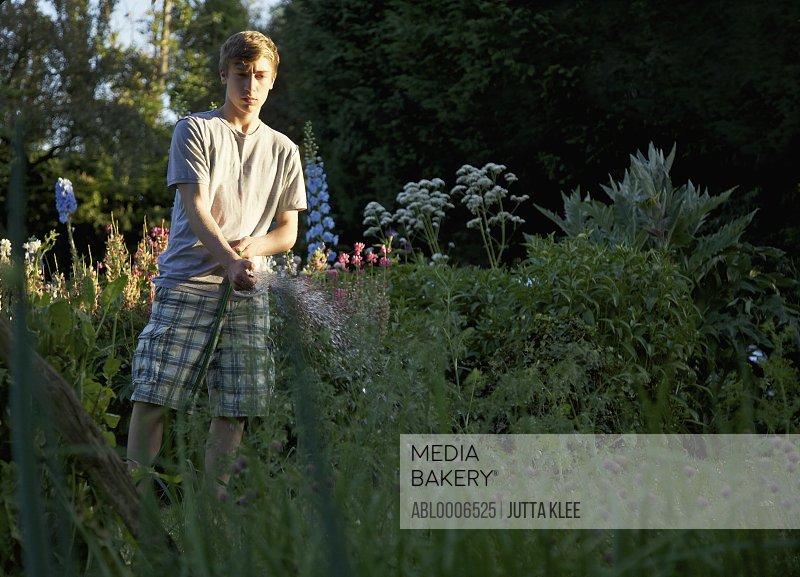 Teenage Boy Watering Plants with Garden Hose