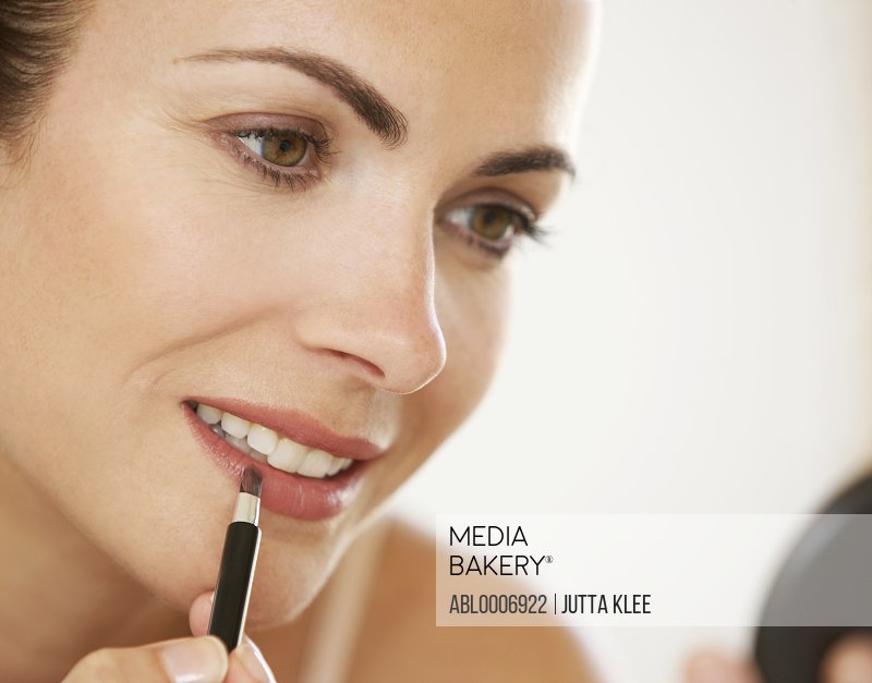 Woman Using Lipstick Brush, Close-up view