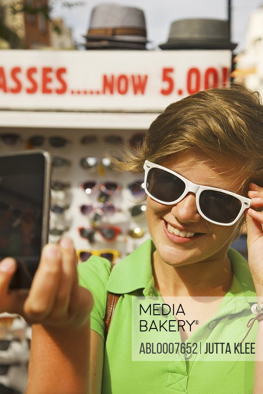 Teenage Girl Trying Sunglasses and  Checking herself on Cell Phone