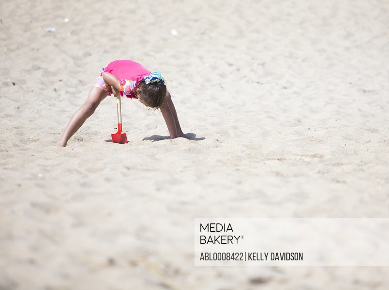 Girl Digging Sand with Toy Shovel