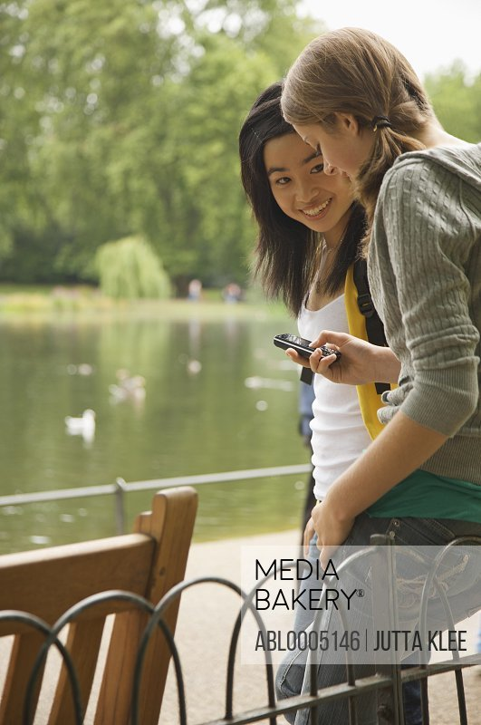 Two teenaged girls using a cell phone in a city park