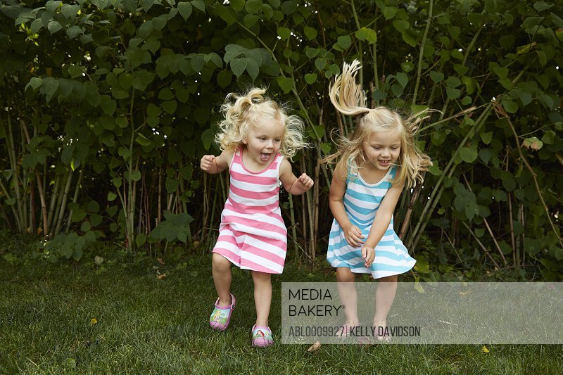 Two Young Girls in Garden Jumping